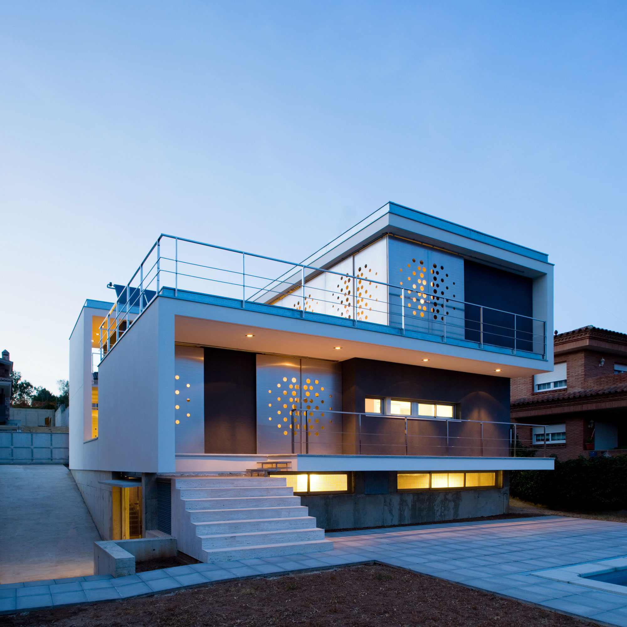backyard-modern-house-design-wth-iron-railings-yellow-lighting-and-steel-wall-with-perforations-plus-terrace-with-cement-block-tiles